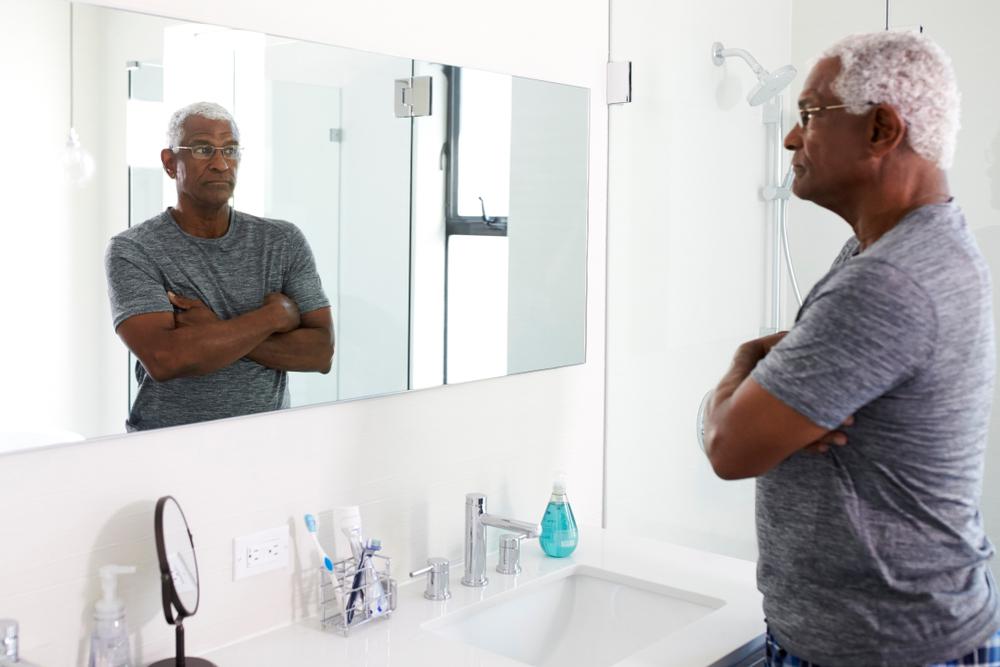 Older man looking in mirror